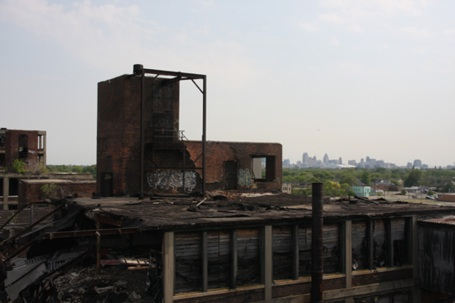 Zicht van op het dak van een vervallen autofabriek; downtown Detroit in de verte