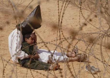 Gevangene troost zijn zoontje. Irak 2003.