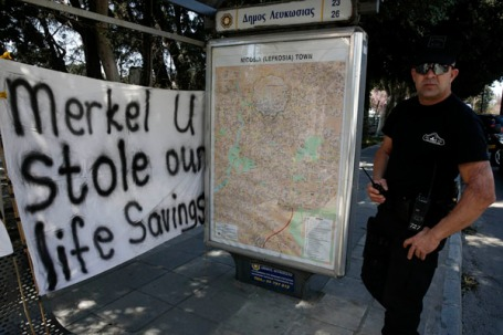 A policeman walks in front of a bus station with an anti-bailout banner outside the parliament in Nicosia