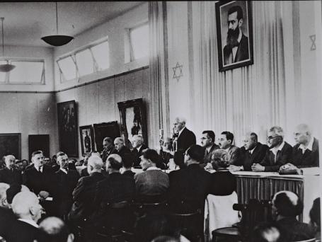 Ben Goerion verklaart Israël onafhankelijk. Boven hem de foto van Theodor Herzl, uitvinder van het Zionisme.