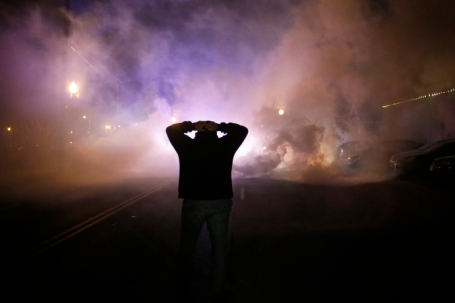 A protester stands with his hands on his head as a cloud of tear gas approaches after a grand jury returned no indictment in the shooting of Michael Brown in Ferguson, Missouri
