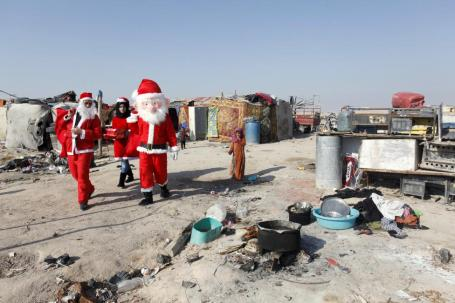 Volunteers wearing Santa Claus costumes distribute presents to the poor in Najaf, south of Baghdad, Iraq December 19, 2015. REUTERS/Alaa Al-Marjani