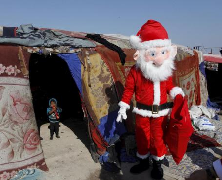 A volunteer wearing a Santa Claus costume distributes presents to children at a poor community in Najaf