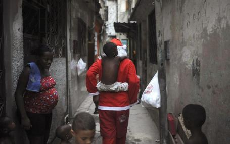 Leandro Wendell dos Santos plays with kids as he walks along the alley of the Mare slums complex to distribute presents to children in Rio de Janeiro