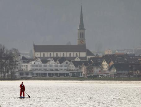 A man dressed as Santa Claus on a stand-up paddle crosses Lake Aegerisee near Unteraegeri