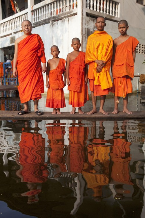 """11 Nov 2011, Bangkok, Thailand --- Prakru Samuteerapisut Sarathamma poses with some novice monks in the flooded Komut Puttarangsi Temple in the Taweewattana District on the western outskirts of Bangkok. This is one of more than 500 Buddhist temples which have been inundated by the recent floods in Thailand. """"I have been in monkhood for 14 years. This is the first time I've experience such a big flood. I knew that the water would come this way. But I didn't expect so much. We just have to accept it. It has been difficult for monks to do our duties. Every day we have to be there to help each other and all the people who have fled here for safety.There are about 200 of them. The officials do come and help us, especially the military. They brought us food and water. Many people who are staying at home also come here to collect food.If it happens again next year, we will have to be more prepared."""" --- Image by © Gideon Mendel/In Pictures/Corbis"""