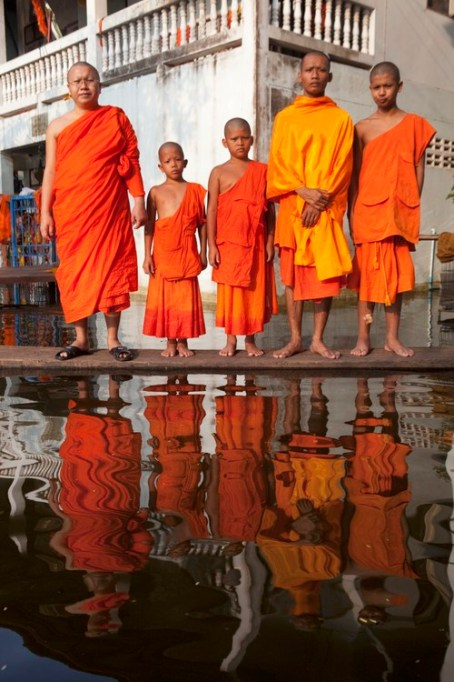 "11 Nov 2011, Bangkok, Thailand --- Prakru Samuteerapisut Sarathamma poses with some novice monks in the flooded Komut Puttarangsi Temple in the Taweewattana District on the western outskirts of Bangkok. This is one of more than 500 Buddhist temples which have been inundated by the recent floods in Thailand. ""I have been in monkhood for 14 years. This is the first time I've experience such a big flood. I knew that the water would come this way. But I didn't expect so much. We just have to accept it. It has been difficult for monks to do our duties. Every day we have to be there to help each other and all the people who have fled here for safety.There are about 200 of them. The officials do come and help us, especially the military. They brought us food and water. Many people who are staying at home also come here to collect food.If it happens again next year, we will have to be more prepared."" --- Image by © Gideon Mendel/In Pictures/Corbis"